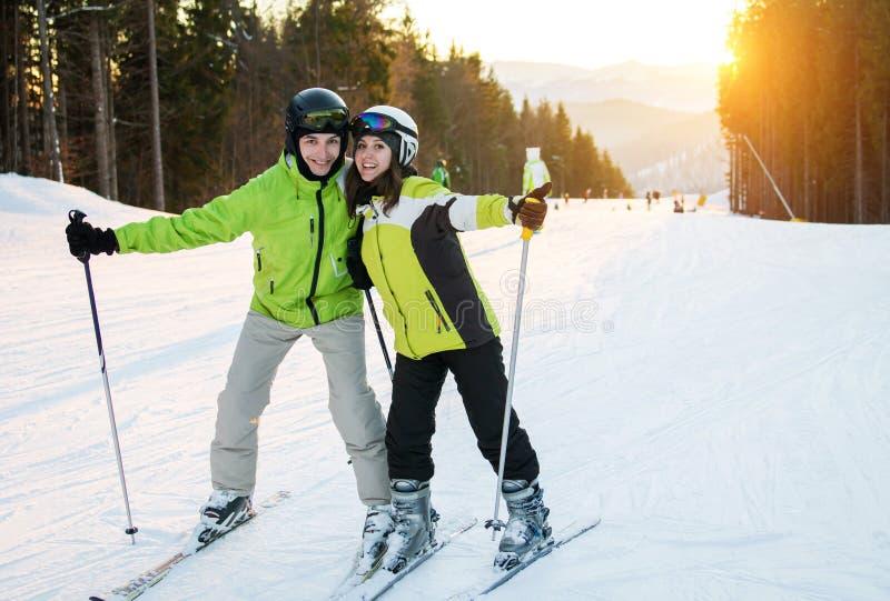 El par joven está esquiando en montañas imagenes de archivo
