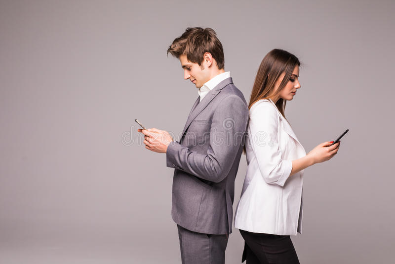 El par joven está utilizando los teléfonos elegantes y está sonriendo mientras que se coloca de nuevo a la parte posterior en un  imagen de archivo