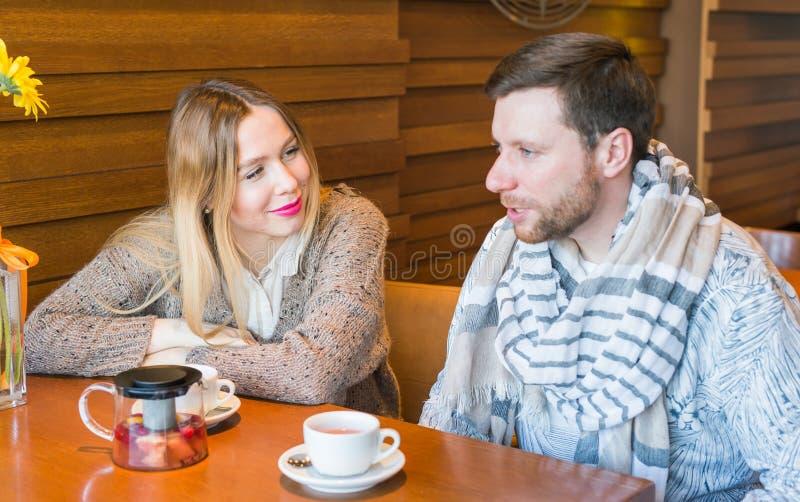El par joven feliz es que habla y de consumición del café y sonriente mientras que se sienta en el café fotos de archivo libres de regalías