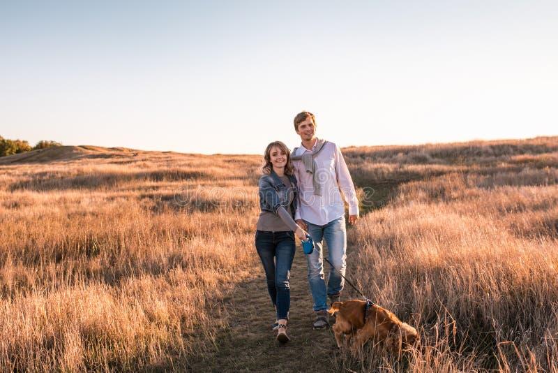 El par joven feliz está caminando con el perro foto de archivo