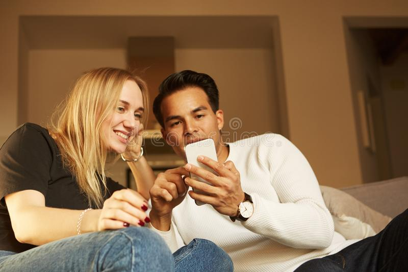 El par joven hermoso en ropa casual está utilizando smartphones, mirando la cámara y la sonrisa fotografía de archivo