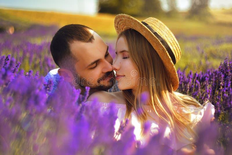 El par joven lindo en amor en un campo de la lavanda florece Disfrute de un momento de felicidad y de amor en un campo de la lava imagenes de archivo