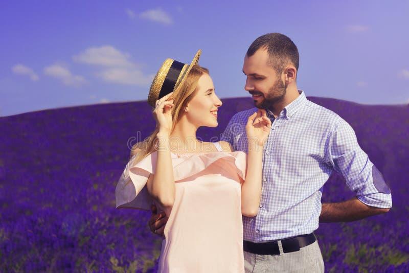 El par joven lindo en amor en un campo de la lavanda florece Disfrute de un momento de felicidad y de amor en un campo de la lava imágenes de archivo libres de regalías
