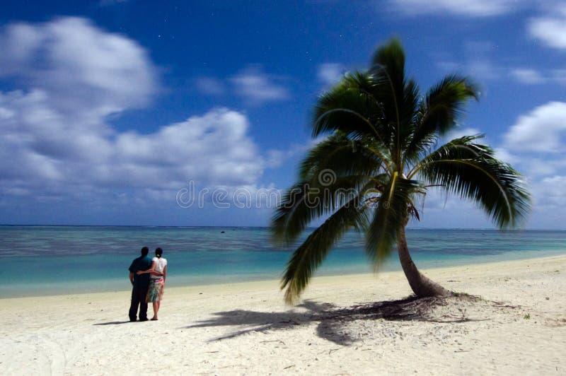 El par joven mira las estrellas en la noche en el isl tropical abandonado imagenes de archivo