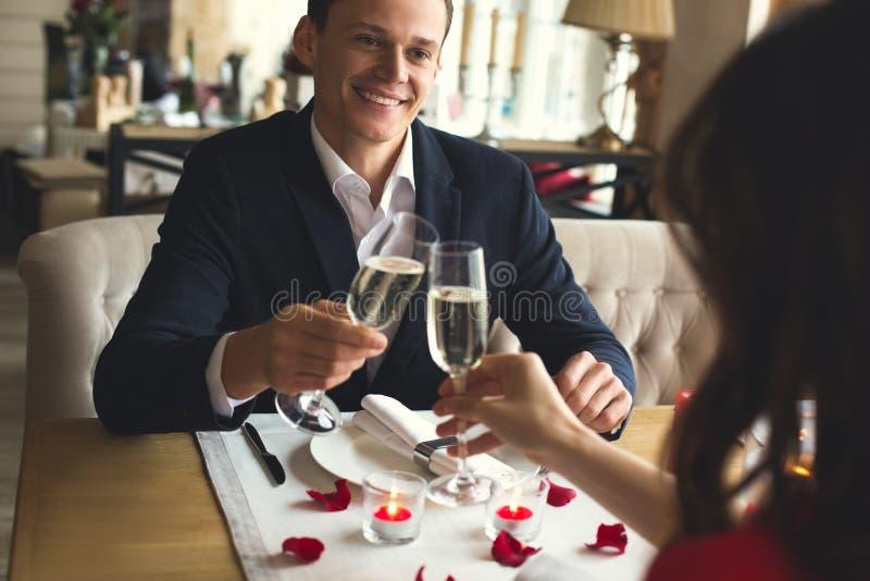 El par joven que cena romántico en el champán de consumición del restaurante anima el filtro foto de archivo