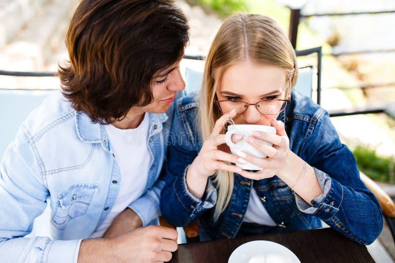 El par joven que se sienta junto en el café, mujer rubia bebe el café fotos de archivo libres de regalías