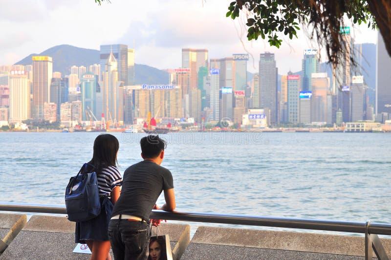 El par joven se está colocando en el puerto que mira la ciudad fotos de archivo libres de regalías