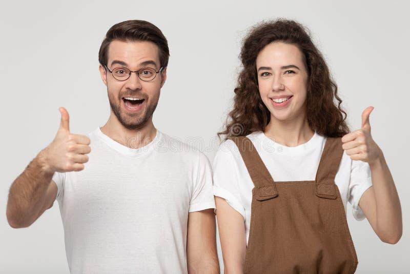 El par joven siente feliz mostrando los pulgares encima del tiro del estudio imágenes de archivo libres de regalías
