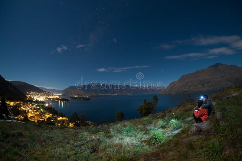 El par joven sube para arriba una colina para mirar Queenstown, Nueva Zelanda en la noche imagen de archivo