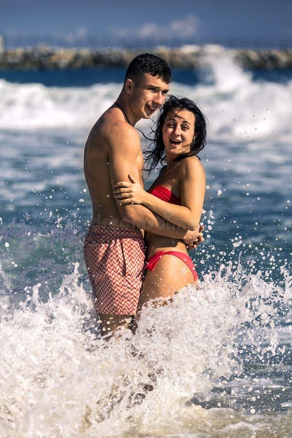 El par joven y atractivo se está divirtiendo en agua en la playa imagenes de archivo