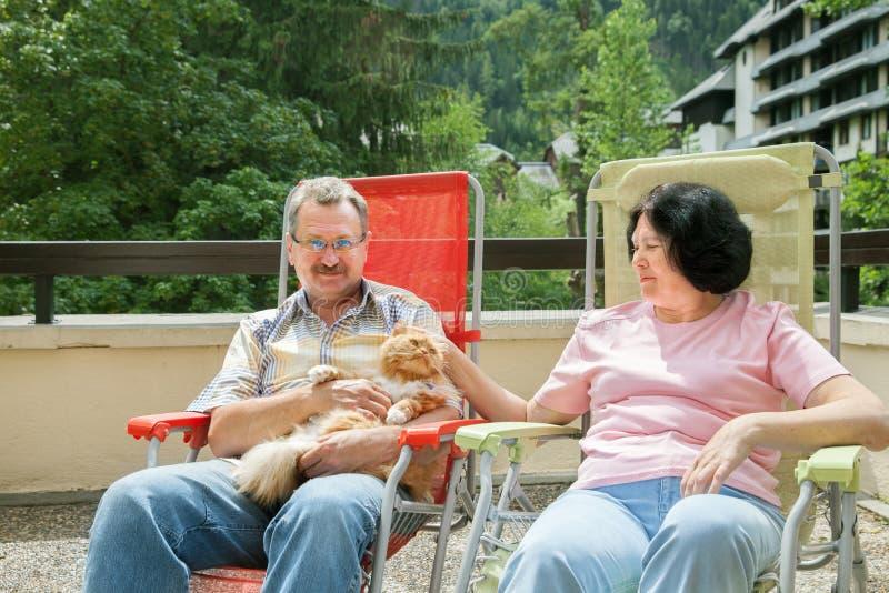 El par maduro se está basando sobre balcón con el gato imagenes de archivo