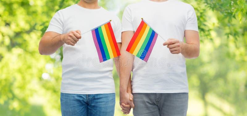 El par masculino con orgullo gay se?ala llevar a cabo por medio de una bandera las manos imagen de archivo