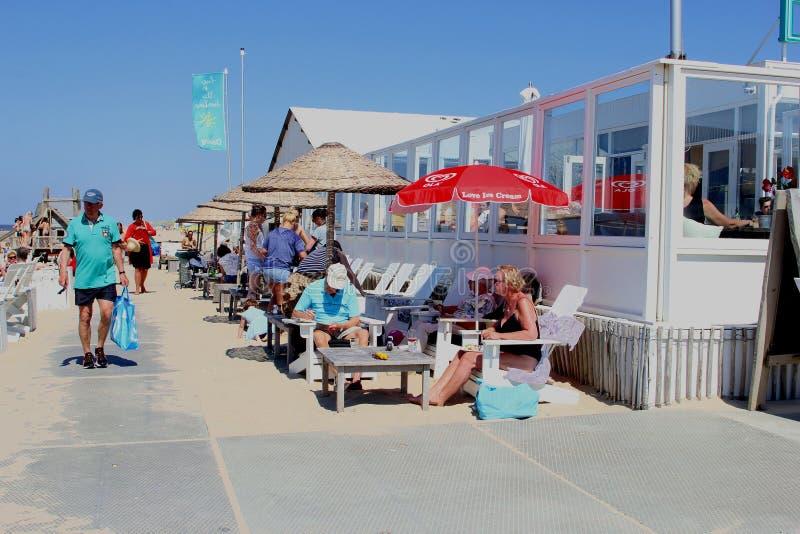 El par mayor goza en una terraza de la playa, Países Bajos fotos de archivo