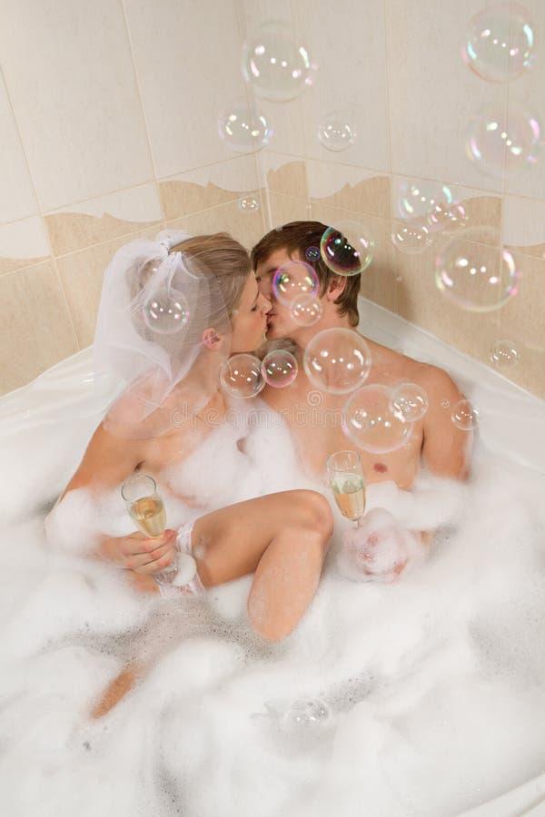 El par que se casa está disfrutando de un baño con las burbujas imagen de archivo libre de regalías