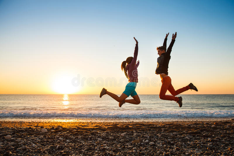 El par salta en la playa sobre salida del sol imagen de archivo