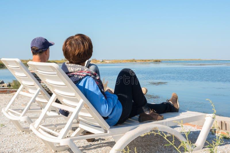 El par se relaja en la playa fotos de archivo