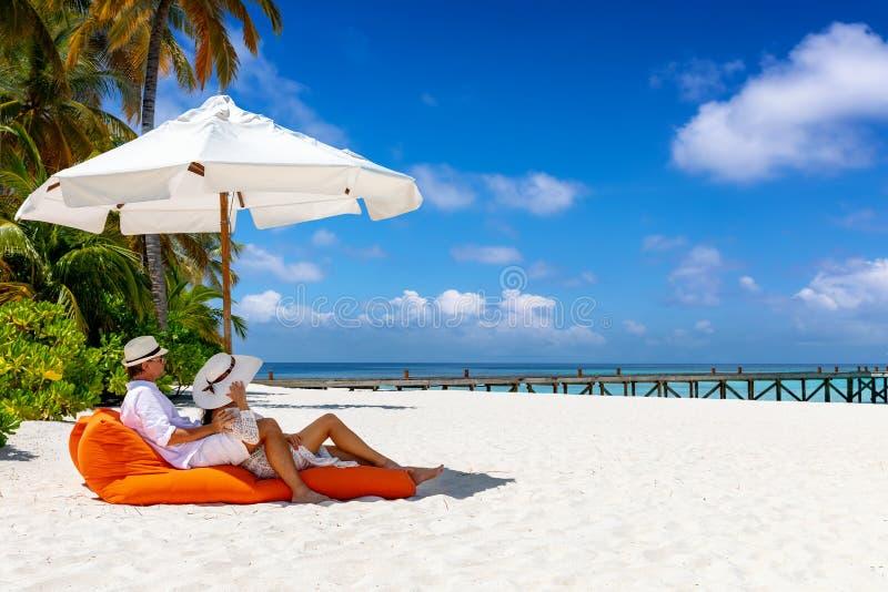 El par se relaja en sunbed en una playa tropical en los Maldivas imagen de archivo