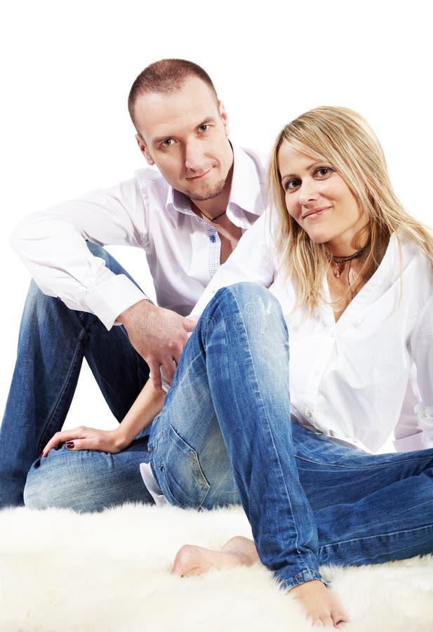 El par se sienta en la alfombra blanca melenuda imagen de archivo libre de regalías