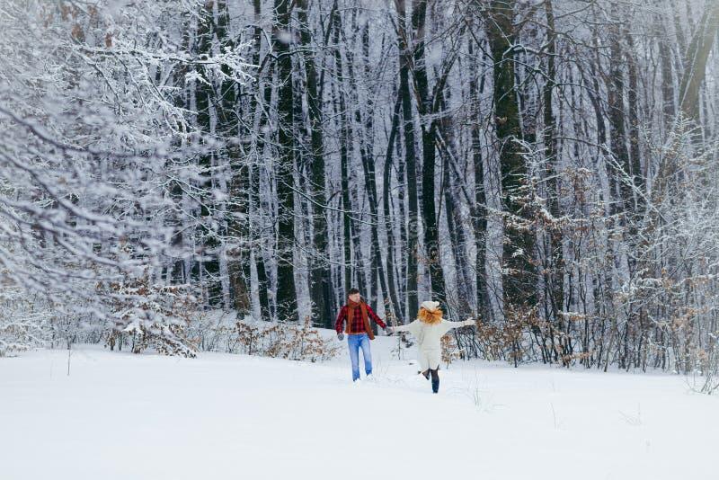 El par sonriente de amor se está divirtiendo mientras que corre a lo largo de la opinión integral del bosque nevoso Tiempo de la  imagen de archivo