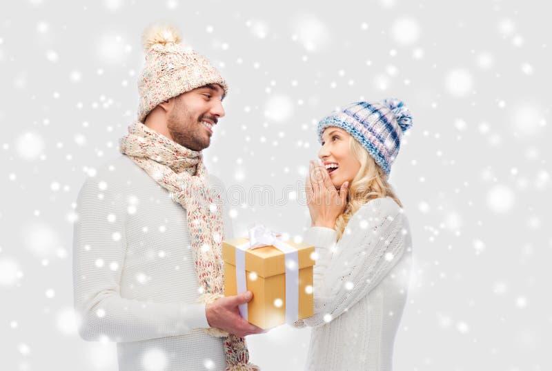 El par sonriente en invierno viste con la caja de regalo imagen de archivo