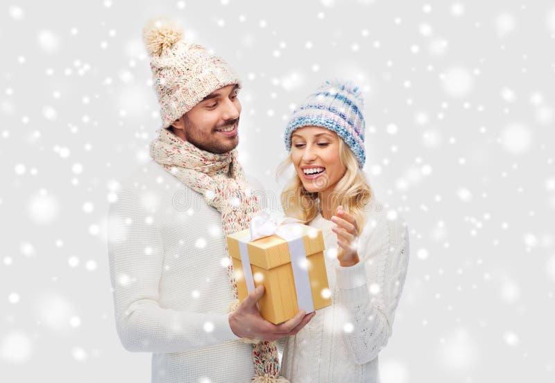 El par sonriente en invierno viste con la caja de regalo imagenes de archivo
