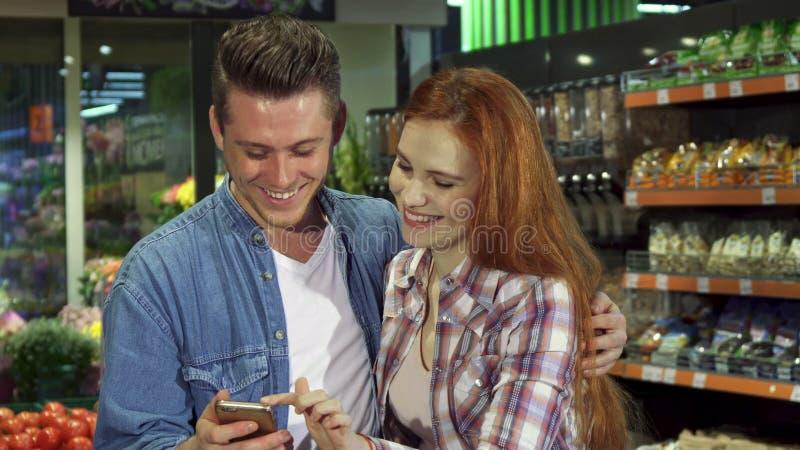 El par utiliza smartphone en el hipermercado imágenes de archivo libres de regalías