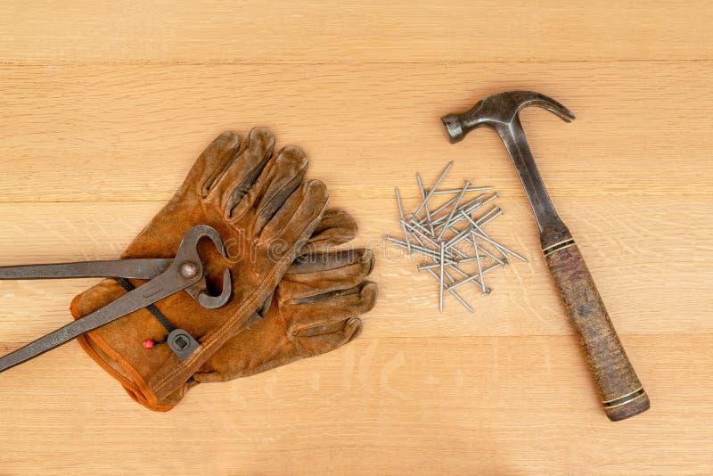 El par vintage de cortar los alicates de las pinzas trabaja guantes que el martillo clava el fondo de madera imágenes de archivo libres de regalías