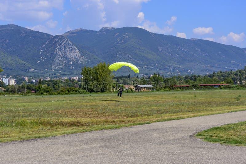 El paracaidista con el paracaídas amarillo aterriza en el campo del vuelo imagen de archivo libre de regalías