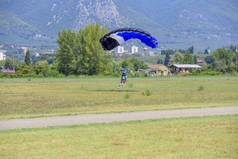 El paracaidista con el paracaídas amarillo aterriza en el campo del vuelo foto de archivo