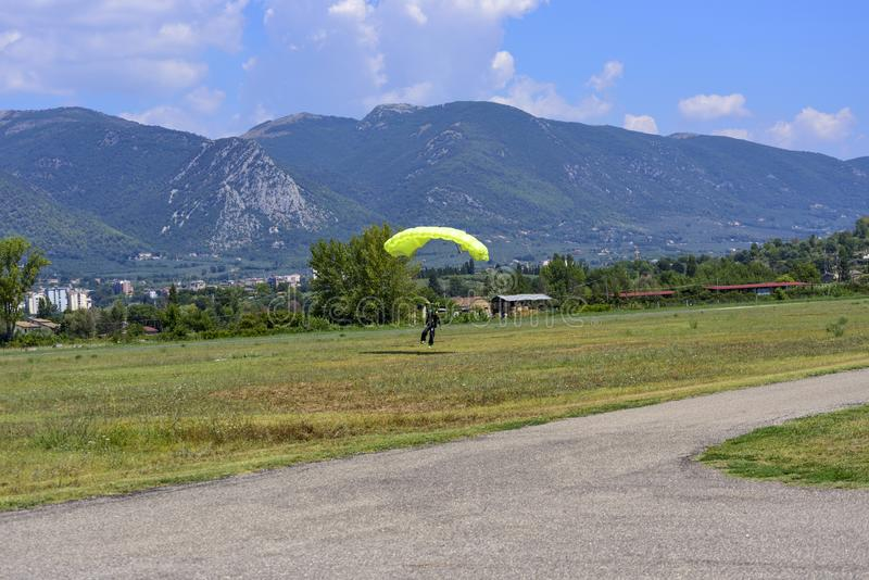 El paracaidista con el paracaídas amarillo aterriza en el campo del vuelo imagen de archivo