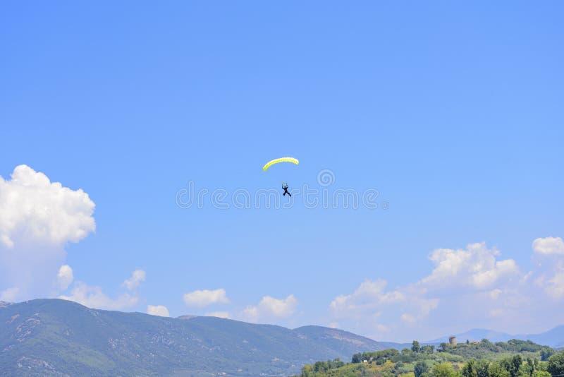 El paracaidista desciende contra un cielo azul, en el fondo el m imágenes de archivo libres de regalías