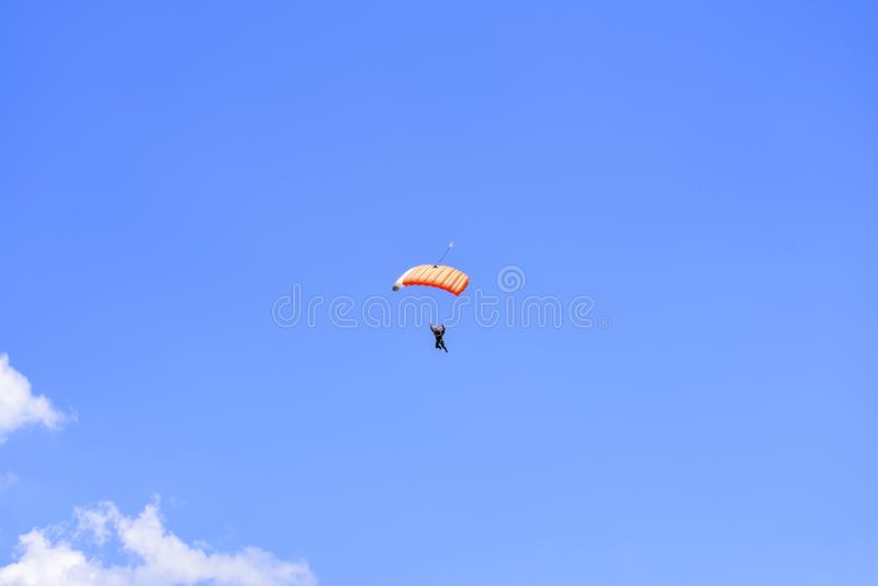 El paracaidista desciende en el cielo azul en un día soleado fotografía de archivo