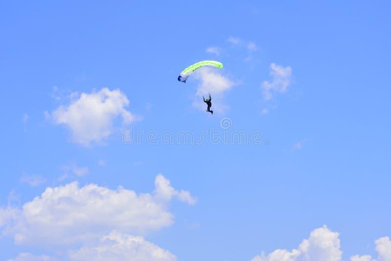 El paracaidista desciende en el cielo azul en un día soleado fotos de archivo libres de regalías