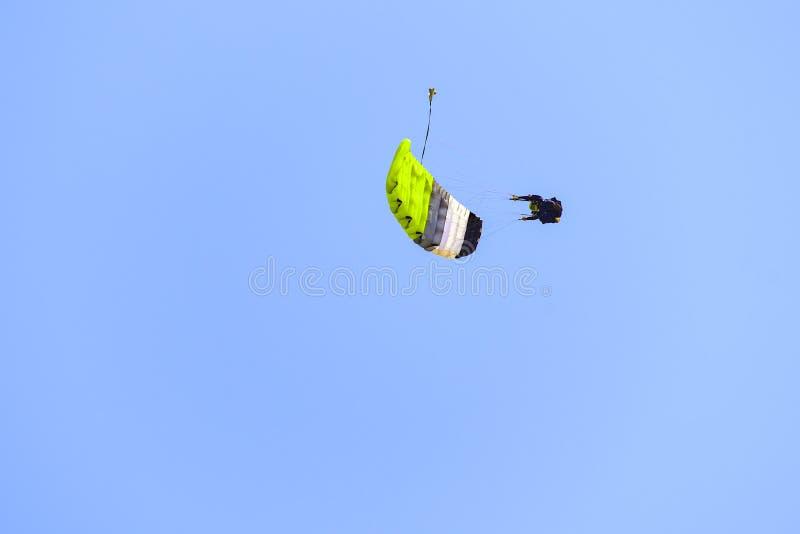 El paracaidista desciende en el cielo azul en un día soleado foto de archivo