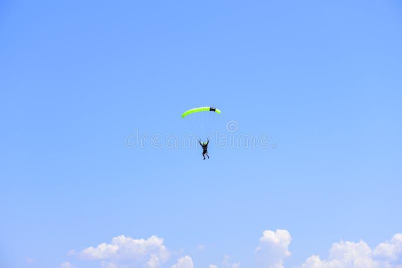 El paracaidista desciende en el cielo azul en un día soleado fotografía de archivo libre de regalías
