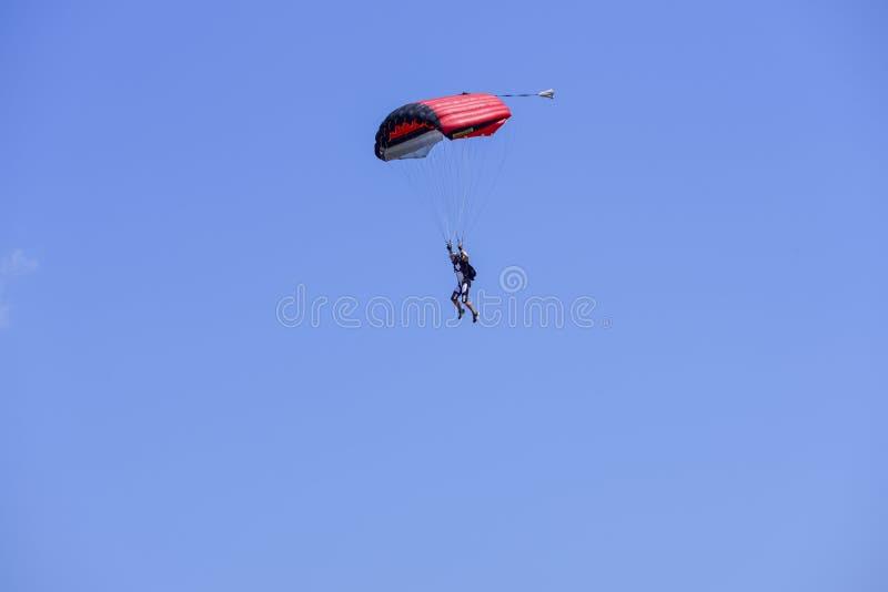 El paracaidista desciende en el cielo azul en un día soleado imagen de archivo libre de regalías