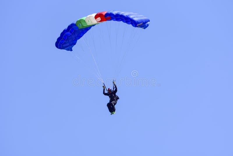 El paracaidista desciende en el cielo azul en un día soleado imagenes de archivo