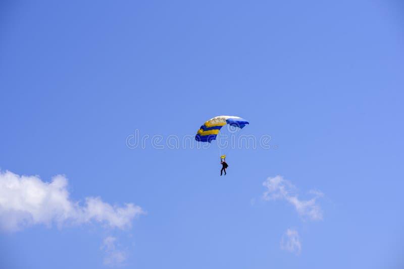 El paracaidista desciende en el cielo azul en un día soleado imágenes de archivo libres de regalías