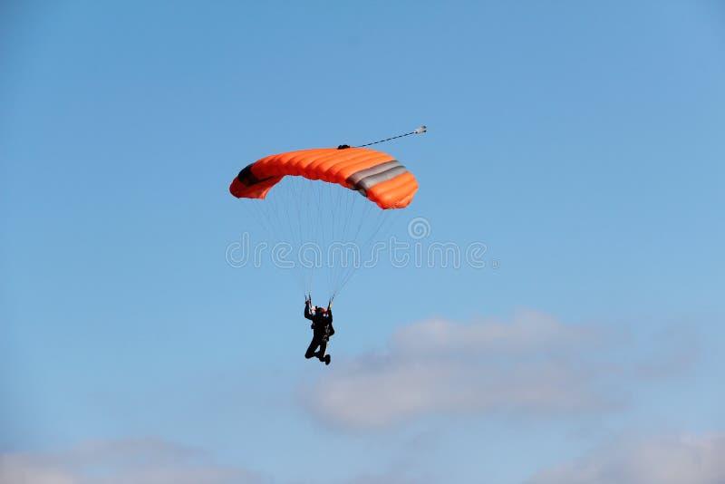 El paracaidista desciende a la tierra foto de archivo