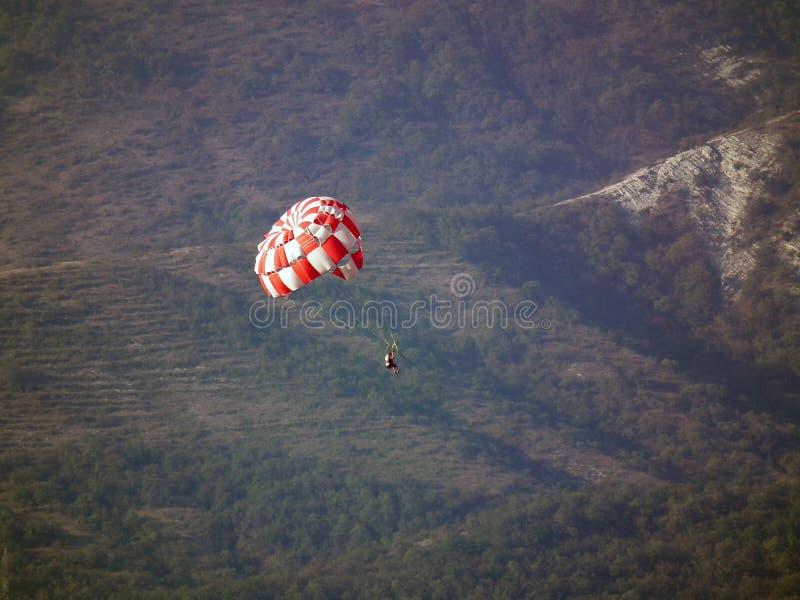 El paracaidista en un paracaídas rojo y blanco desciende contra el contexto de las montañas del bosque foto de archivo libre de regalías