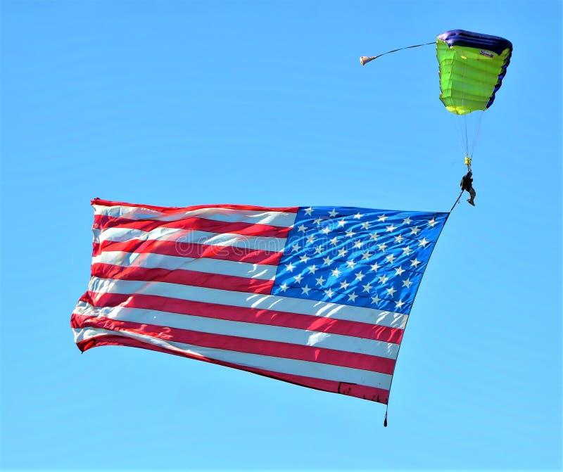El paracaidista que reduce deslizamientos a la tierra mientras que remolca una bandera americana grande fotos de archivo