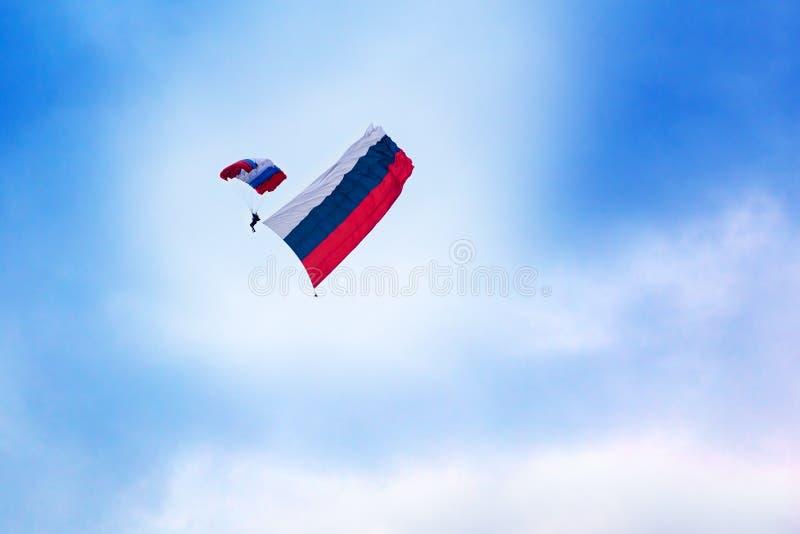 El paracaidista ruso salta con un paracaídas pintado en los colores de la bandera de Rusia con la bandera rusa en el cielo azul c imagenes de archivo