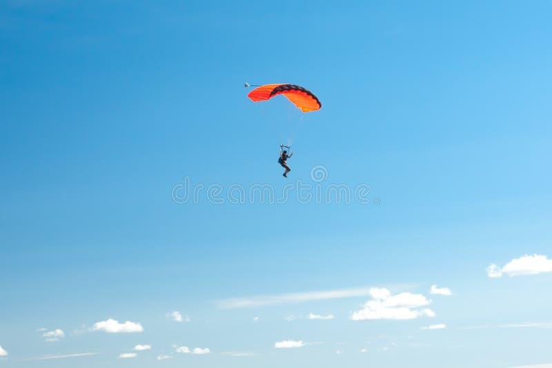 El paracaidista se eleva en los paracaídas coloridos a través del cielo azul ilimitado contra la perspectiva de las nubes mullida foto de archivo libre de regalías