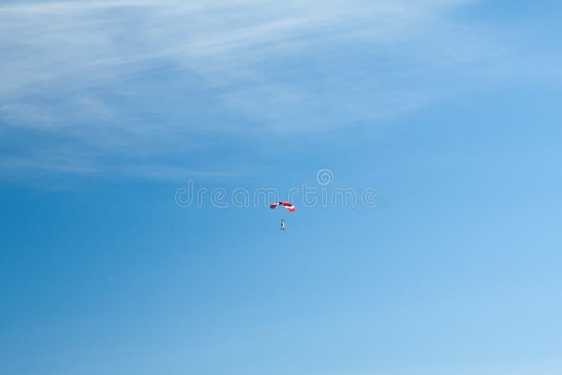 El paracaidista se eleva en los paracaídas coloridos a través del cielo azul ilimitado contra la perspectiva de las nubes mullida foto de archivo