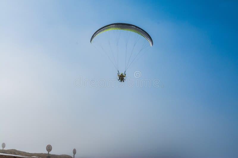 El paracaidista vuela contra el cielo azul Paraca?das motorizado imagen de archivo