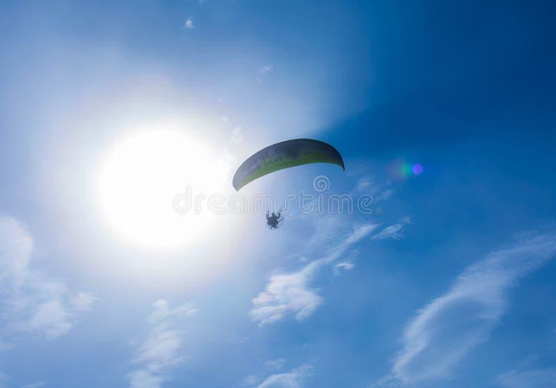 El paracaidista vuela contra el cielo azul Paraca?das motorizado fotografía de archivo libre de regalías