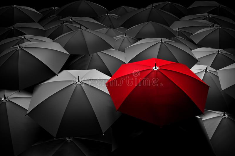El paraguas rojo se destaca de la muchedumbre Diferente, líder foto de archivo