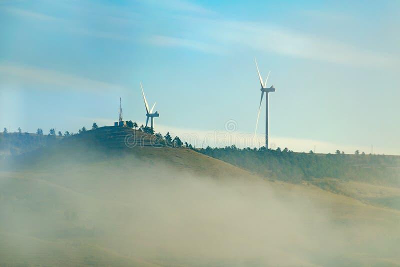El parque eólico de dos turbogeneradores del viento encendido remata una colina, madrugada, nube de la niebla imágenes de archivo libres de regalías