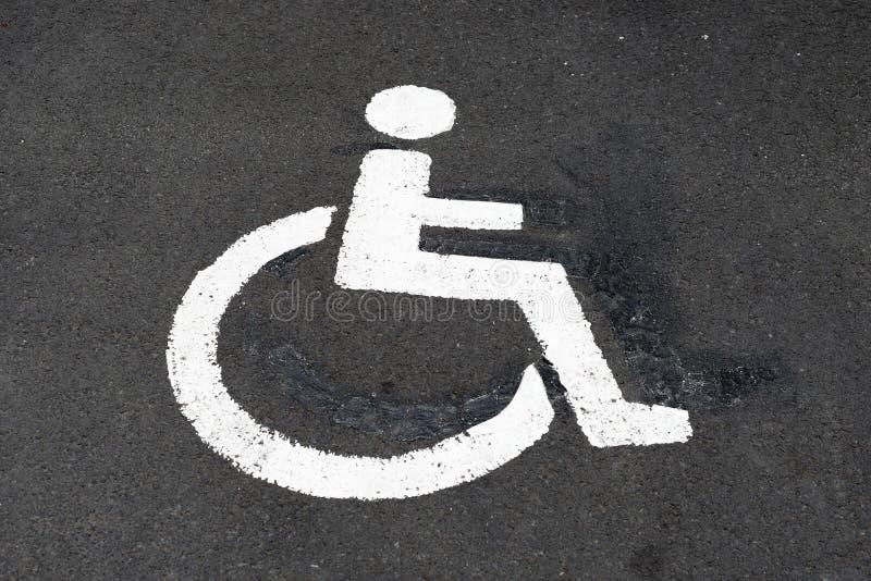 El parquear perjudicado, símbolo discapacitado en asfalto fotos de archivo