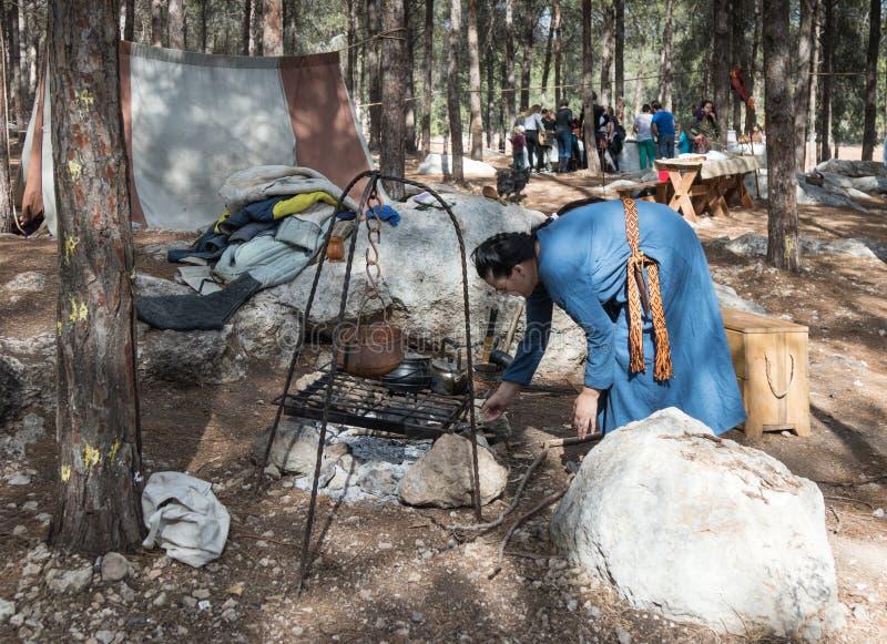 El participante de la reconstrucción del ` de Viking Village del ` enciende un fuego en el hogar en el campo en el bosque cerca d foto de archivo libre de regalías